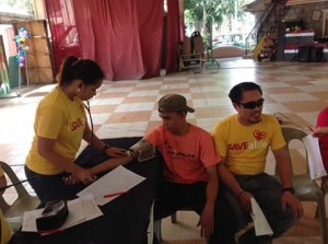 Goducate staff (in yellow) taking blood pressure